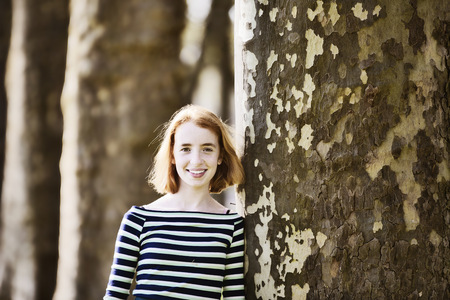 Smiling girl leaning ageinst tree trunk