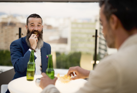 Men on roof terrace drinking beer and eating chips