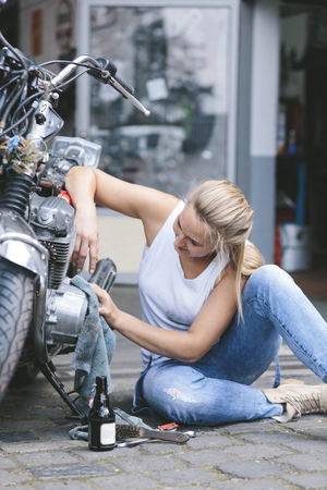 Young woman cleaning motorbike LANG_EVOIMAGES