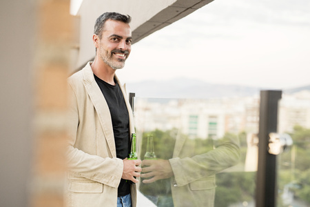 Portrait of smiling man standing on roof terrace with beer bottle