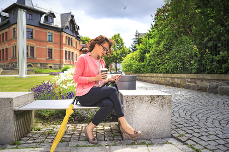 Woman with coffee to go resting on a bench looking at cell phone LANG_EVOIMAGES