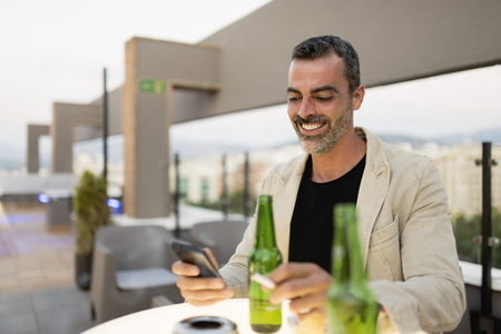 Portrait of smiling man standing on roof terrace with beer bottles and cigarette looking at cell phone