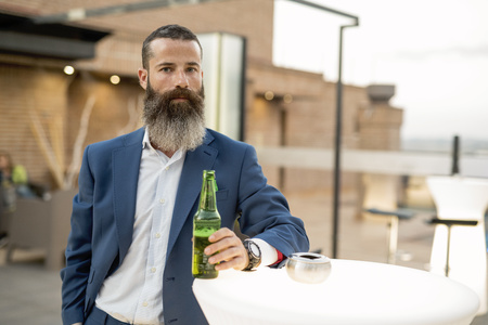 Portrait of bearded businessman drinking beer on a terrace LANG_EVOIMAGES