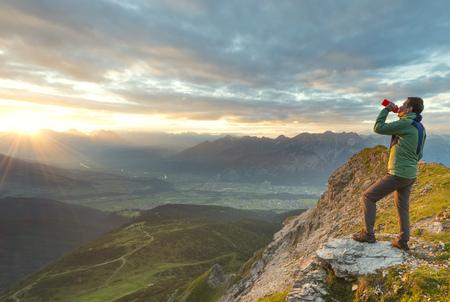 Austria, Tyrol, hiker drinking, sunset LANG_EVOIMAGES