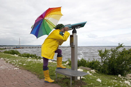 Germany, Steinhuder Meer, woman wearing yellow Wellington boots and rain coat looking through telescope LANG_EVOIMAGES