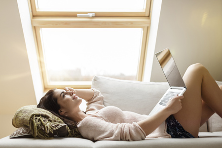 Relaxed woman lying on couch using laptop