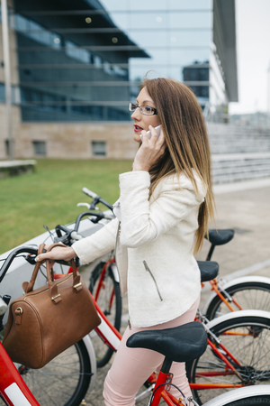 Businesswoman with bicycle on cell phone