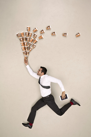 Businessman running with coffee and tablet LANG_EVOIMAGES