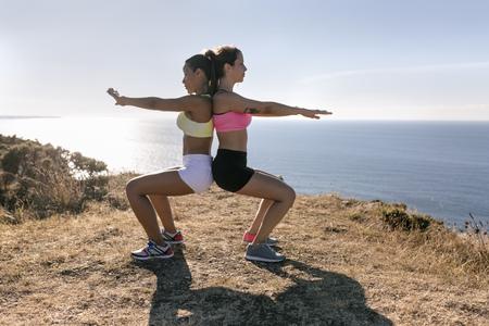 Spain, Asturias, two sportswomen training on the coast, back to back