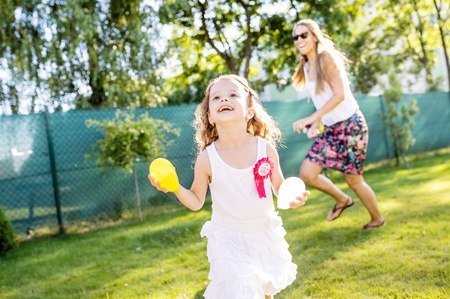 Little girl having fun with water bombs in the garden LANG_EVOIMAGES