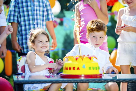 Little girl and little boy celebrating birthday in the garden with friends and family