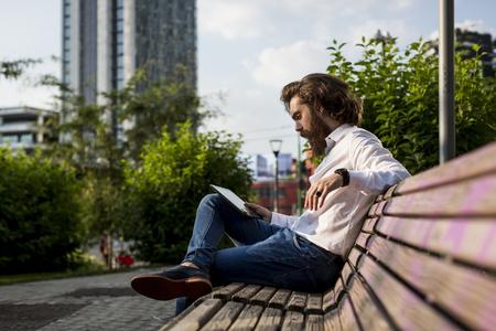 Stylish businessman sitting on bench using digital tablet