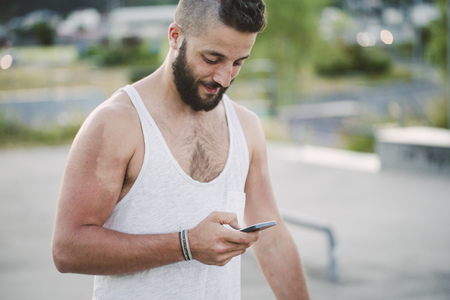 Young man with shaved head looking at cell phone LANG_EVOIMAGES