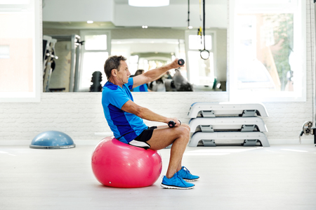 Senior man exercising with dumbbells on fitness ball in gym LANG_EVOIMAGES