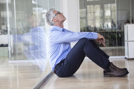 Mature businessman sitting on floor in office LANG_EVOIMAGES