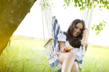 Happy woman with apple relaxing in a hanging chair under a tree LANG_EVOIMAGES