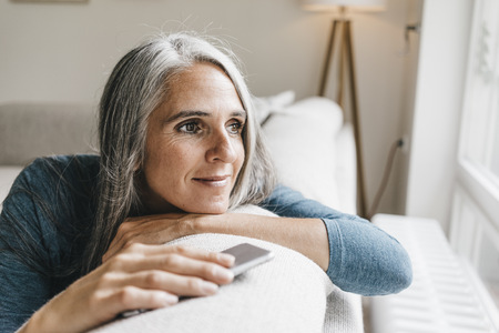 Smiling woman sitting on the couch looking through window