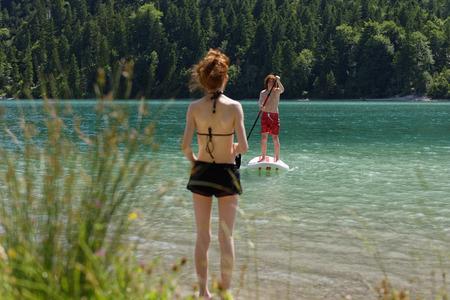 Austria, Tyrol Ammergau Alps, Plansee, Teenage boy standing on paddleboard, sister waiting on lakeshore