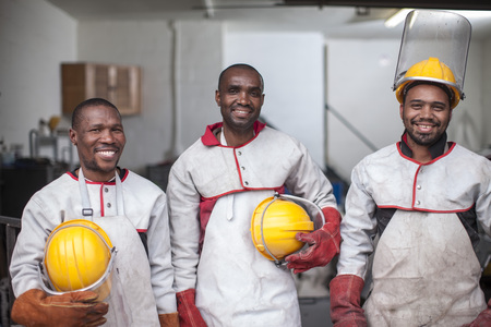 Portrait of three smiling workers with safety helmets LANG_EVOIMAGES