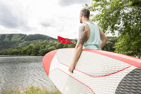 Man carrying stand up paddle board at lakeside