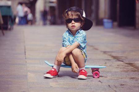 Portrait of little boy sitting on  skateboard wearing oversized sunglasses and basecap