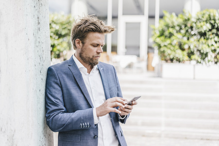 Businessman looking on cell phone