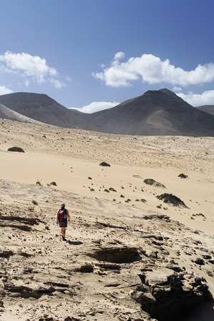Spain,Canary Islands,Fuerteventura,Jandia,El Jable,Barlovento,Hiker Walking Through Sand Dune