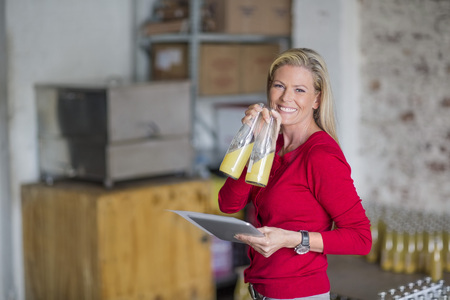 Smiling woman holding tablet testing juice bottles in warehouse
