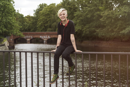 Laughing young woman sitting on railing in front of a canal LANG_EVOIMAGES