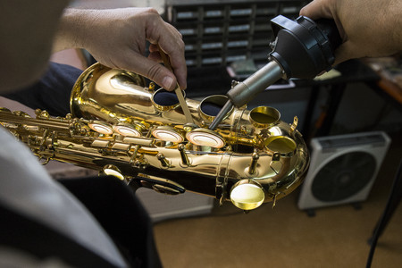 Instrument maker heating with a machine the keys of a saxophone during a repair