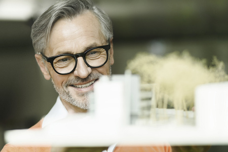 Portrait of smiling man looking at architectural model