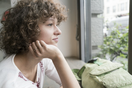 Young woman looking through window LANG_EVOIMAGES