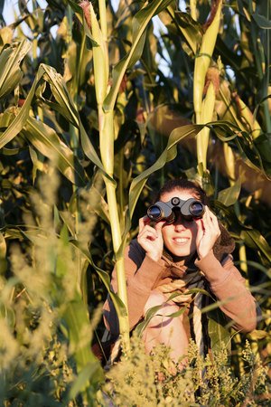 Woman hiding in cornfield and watching something with binoculars