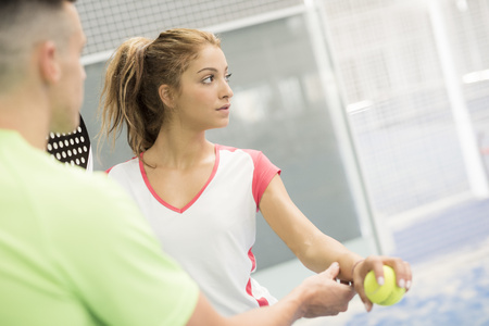 Man teaching woman in paddle tennis LANG_EVOIMAGES
