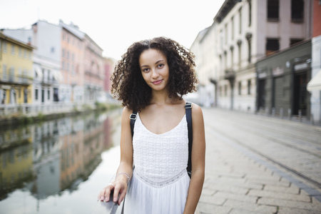 Italy, Milan, portrait of smiling young woman with curly brown hair