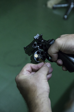 Hands of a man reloading a revolver with bullets