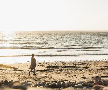 France, Crozon peninsula, woman walking on beach at sunset