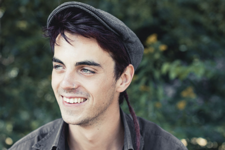 Portrait of smiling young man with nose piercing wearing cap LANG_EVOIMAGES
