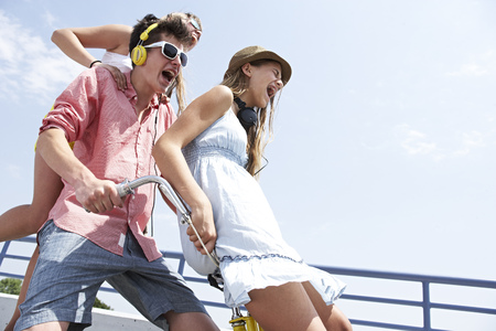 Three happy teenage friends screaming outdoors LANG_EVOIMAGES
