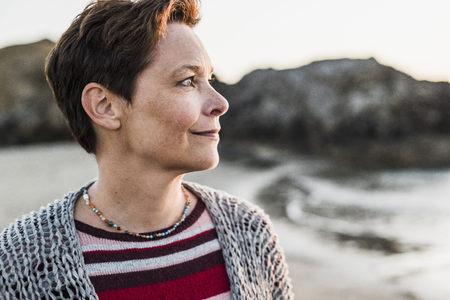 France, Crozon peninsula, portrait of woman on the beach at sunset