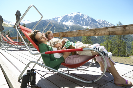 Family relaxing on panorama terrace in the mountains