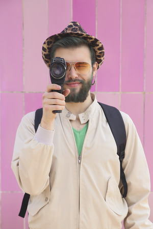 Young man using a vintage video camera filming viewer