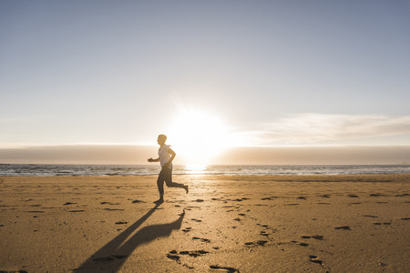 France, Bretagne, Crozon peninsula, woman running on beach at sunset LANG_EVOIMAGES
