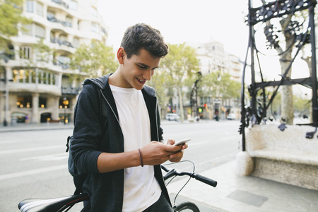 Teenager with a bike in the city, using smartphone LANG_EVOIMAGES