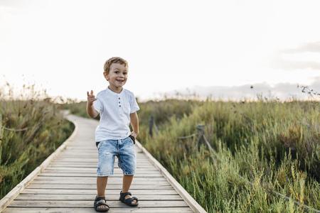 Happy little boy standing on boardwalk in nature LANG_EVOIMAGES