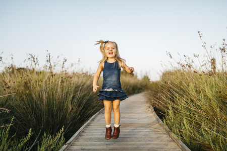 Happy little girl jumping on boardwalk in nature