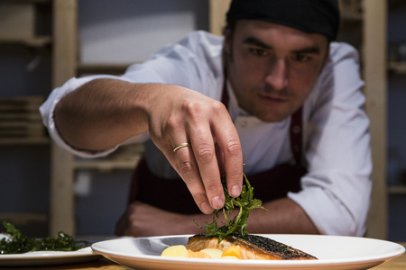 Chef decorating a slice of salmon with arugula