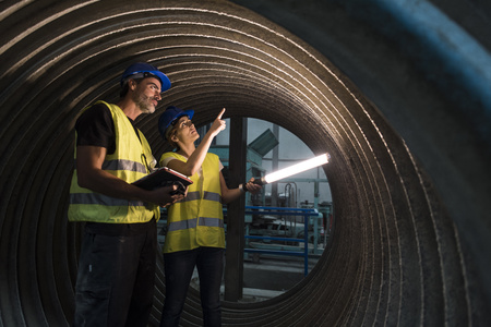 Man and woman examining giant construction tube LANG_EVOIMAGES