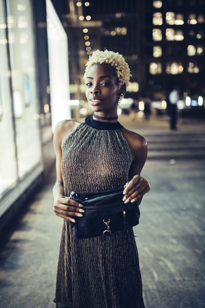 Portrait of young woman with handbag wearing evening dress LANG_EVOIMAGES