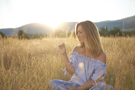 Blond woman sitting on meadow at backlight